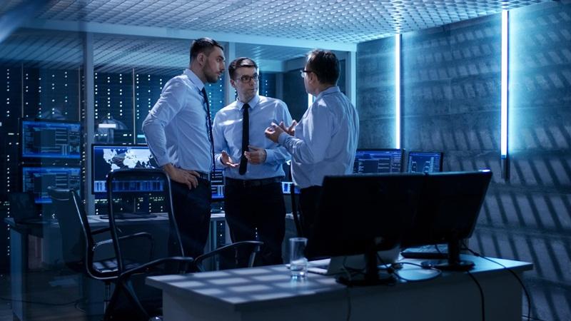 Trio de empresários de terno conversando